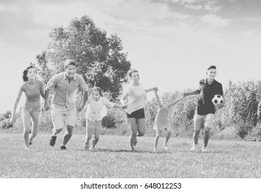 Cheerful young parents with four children are being active and running in park on summer day