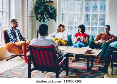 Cheerful young people dressed in casual wear laughing during game sitting on comfortable couch in modern hostel.Positive hipster guys having fun spending free time together in stylish apartment