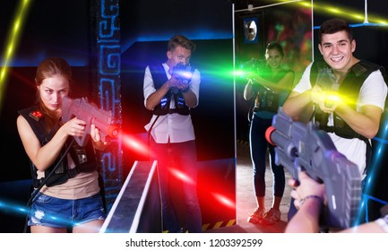 Cheerful young people enthusiastically playing lasergames in dark room (first-person view)