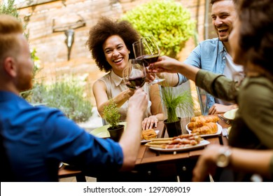 Cheerful young people have lunch in the courtyard and toasting with red wine