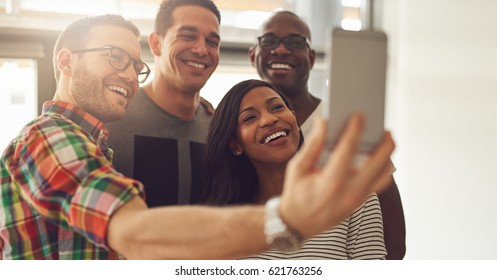 Cheerful young people in the office smiling and taking the selfie.