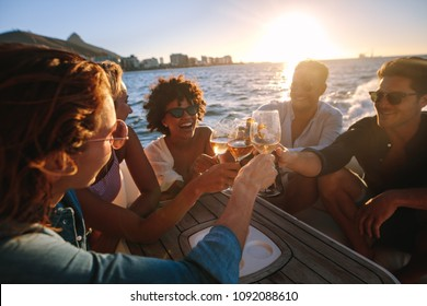 Cheerful young people on yacht drinking together. Group of friends toasting drinks and having party on boat.
