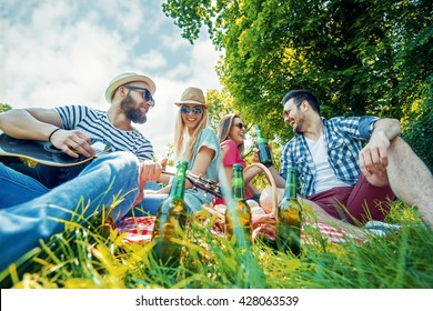 Cheerful young people in the park having picnic and playing guitar