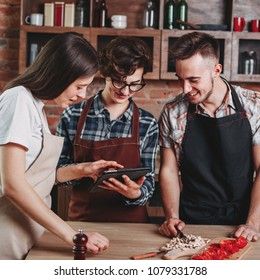 Cheerful young people reading recipe on tablet pc. Friends having fun while preparing dinner. Cooking class, culinary, friendship, togetherness, food and people concept