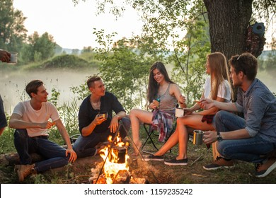 cheerful young people warming near the camp fire. warmth concept. unforgettable moments with best friends