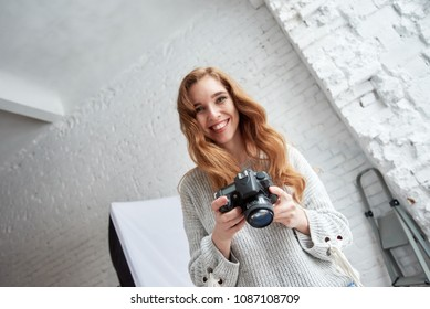 Cheerful young photographer with digicam laughing during photo session