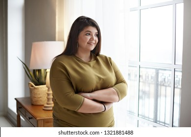 Cheerful young plus size overweight woman with black hair and chubby cheeks crossing arms on her chest and smiling happily, standing by window, looking outside, contemplating beautiful morning view