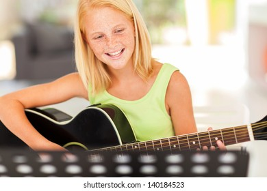 cheerful young pre teen musician playing guitar