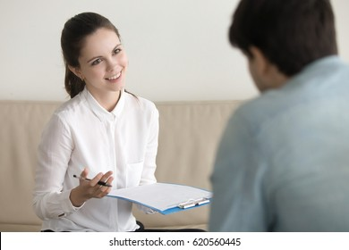 Cheerful young psychotherapist consulting man, HR manager wearing white shirt holding resume, asking questions, interviewing a man sitting his back, business meeting with client