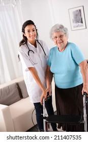 cheerful young rehab nurse helping elderly woman using a walker