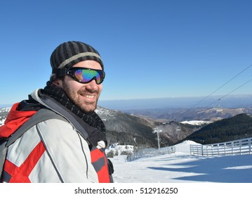 Cheerful young skier at the starting position at the top of the ski slope, ready for skiing down the hill, ski resort Kopaonik, Serbia