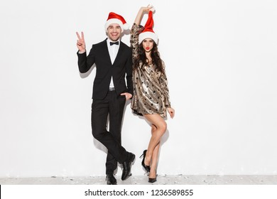 Cheerful young smartly dressed couple wearing red hats celebrating New Year party isolated over white background