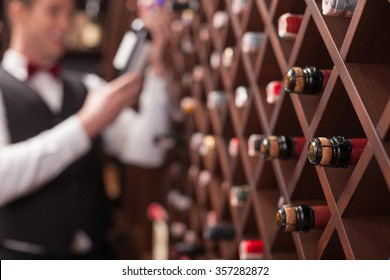 Cheerful young sommelier is choosing wine in cellar. He is smiling. Focus on bottles in shelf