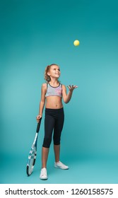 Cheerful young sports girl playing tennis isolated over blue background