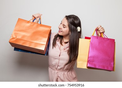 Cheerful young student holds shopping bags