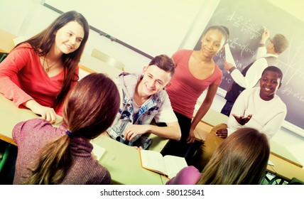 Cheerful young students of different nationalities sitting and smiling in the classroom while the break