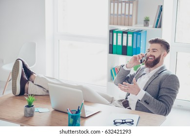Cheerful young successful man is talking on the phone at the workplace with feet on the table.He is wearing formal wear and gesturing