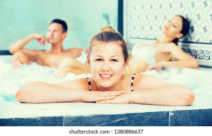 Cheerful  young  three friends relaxing enjoying jacuzzi hot tub bubble bath in spa complex