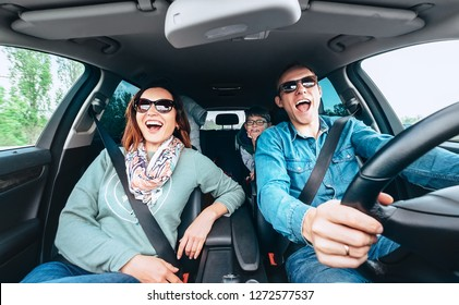 Cheerful young traditional family has a long auto journey and singing aloud the favorite song together. Safety riding car concept wide angle inside car view image.