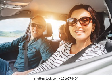 Cheerful young traditional family has a long auto journey and smiling together. Safety riding car concept inside car wide angle view image.