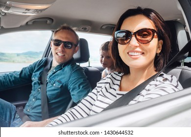Cheerful young traditional family has a long auto journey and smiling together. Safety riding car concept inside car wide angle view.