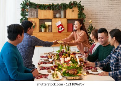 Cheerful young Vietnamese people having dinner on Christmas night