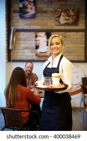 Cheerful young waitress holding tray, smiling happy, looking at camera.