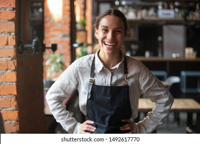 Cheerful young waitress wearing apron laughing looking at camera, happy businesswoman small business owner of girl entrepreneur cafe employee posing in restaurant coffee shop interior, portrait