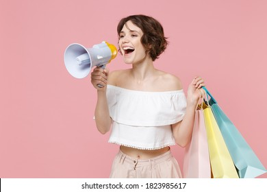 Cheerful young woman 20s in summer clothes isolated on pastel pink background studio portrait. Shopping discount sale concept. Mock up copy space. Hold package bag with purchases scream in megaphone