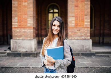 Cheerful young woman with backpack and notebooks standing and smiling in park