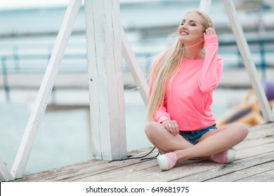 Cheerful young woman at beach smiling outdoor portrait. Blonde beautiful hipster girl wear shorts and pink blouse posing at sea dock. Pretty blond romantic lady at seaside with flying hair outdoors.