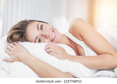 Cheerful Young Woman in Bed