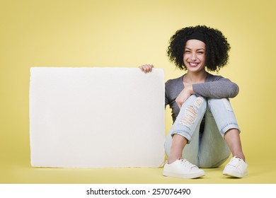 Cheerful young woman being happy presenting a blank white paper sign board