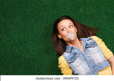 Cheerful young woman blowing bubble gum and thinking about something while lying on the grass.Woman blowing bubble gum and thinking
