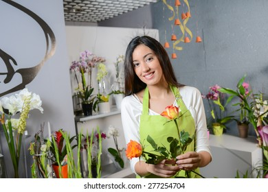 cheerful young woman brunette florist selling flowers in a flower shop