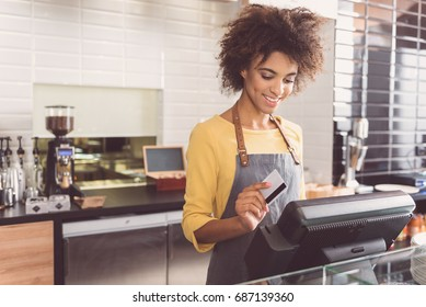 Cheerful young woman cashier is working in cafe