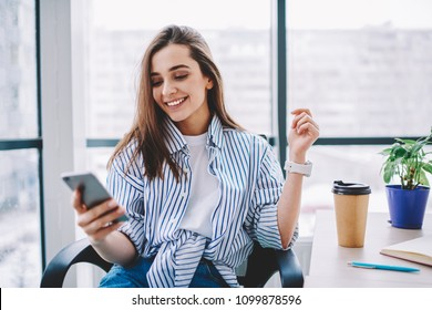 Cheerful young woman checking new feed and content in social networks via smartphone during coffee break in office,happy cute female blogger satisfied with followers messages sitting at desktop