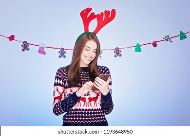 Cheerful young woman in Christmas outfit smiling, using smart phone. Closeup, studio lighting.