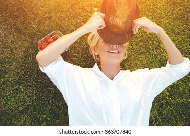 Cheerful young woman closes own eyes from the sunlight using stylish hat while enjoying summer vacation, hipster girl with beautiful smile hiding face under headgear while lying on the grass in park