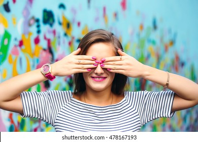 cheerful young woman covering her eyes with her hands with a nice manicure on the background of bright walls
