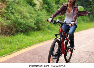 cheerful young woman cyclist cycling on forest trail