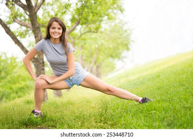 Cheerful young woman doing exercises in park
