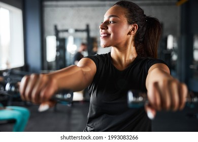 Cheerful young woman doing upperbody workout indoors