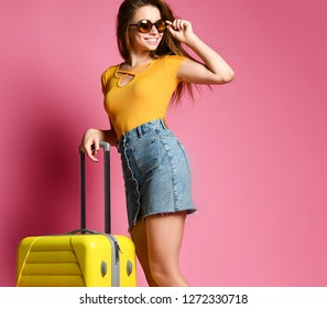 cheerful young woman dressed in summer clothes and sunglasses standing with a suitcase isolated over pink background