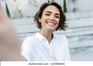 Cheerful young woman in earphones standing at the street, taking a selfie