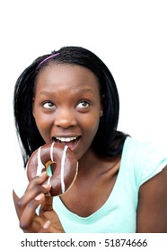 Cheerful young woman eating a chocolate donut against a white background
