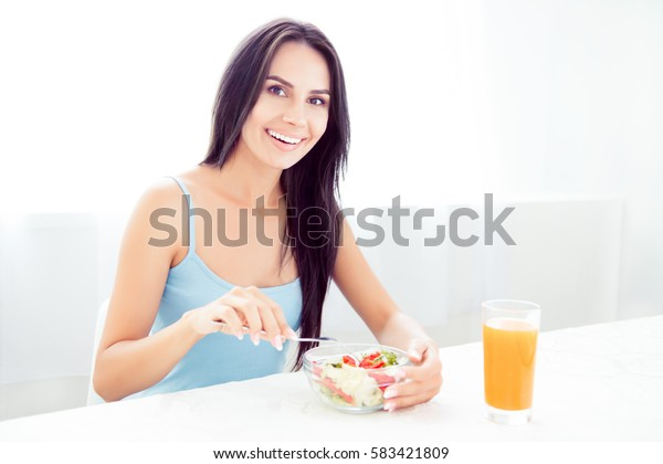A cheerful young woman eating fresh organic salad and drinking orange juice for breakfast