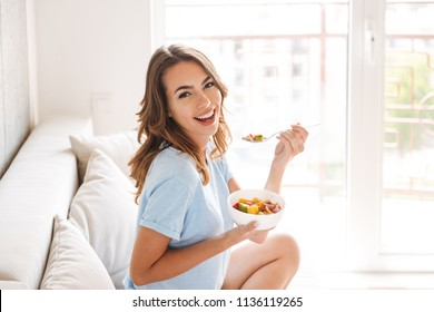 Cheerful young woman eating healthy breakfast while sitting on a couch at home