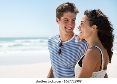 Cheerful young woman enjoying at beach while man looking at her. Smiling husband looking at beautiful wife at seaside. Loving young man with his girlfriend standing together at sea with copy space.