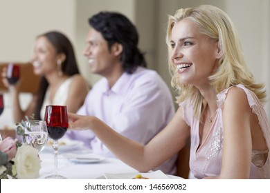 Cheerful young woman enjoying dinner party with friends